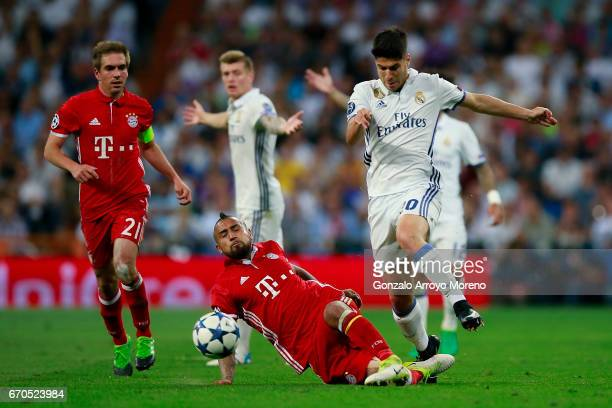 Arturo Vidal of Bayern Muenchen tackles Marco Asensio of Real Madrid CF during the UEFA Champions League Quarter Final second leg match between Real...