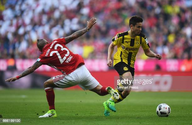 Arturo Vidal of Bayern Muenchen tackles Raphael Guerreiro of Borussia Dortmund during the Bundesliga match between Bayern Muenchen and Borussia...