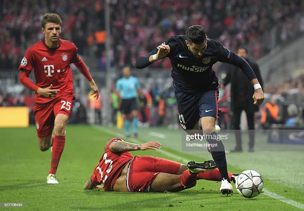 Arturo Vidal of Bayern Munich slides to tackle Yannick Carrasco of Atletico Madrid during UEFA Champions League semi final second leg match between FC Bayern Muenchen and Club Atletico de Madrid at Allianz Arena on May 3, 2016 in Munich, Germany.