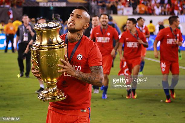 Arturo Vidal of Chile celebrates with the trophy after winning the championship match between Argentina and Chile at MetLife Stadium as part of Copa...