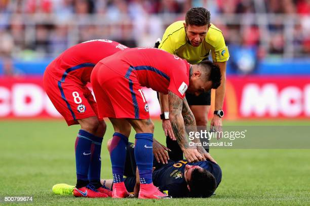 Arturo Vidal of Chile Eduardo Vargas of Chile and referee Gianluca Rocchi tend to Ryan McGowan of Australia during the FIFA Confederations Cup Russia...