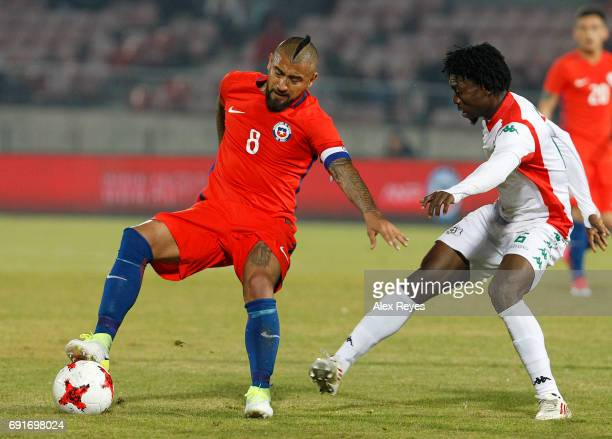 Arturo Vidal of Chile fights for the ball with Junior Sylla of Burkina Faso during a match between Chile and Burkina Faso as part of an International...