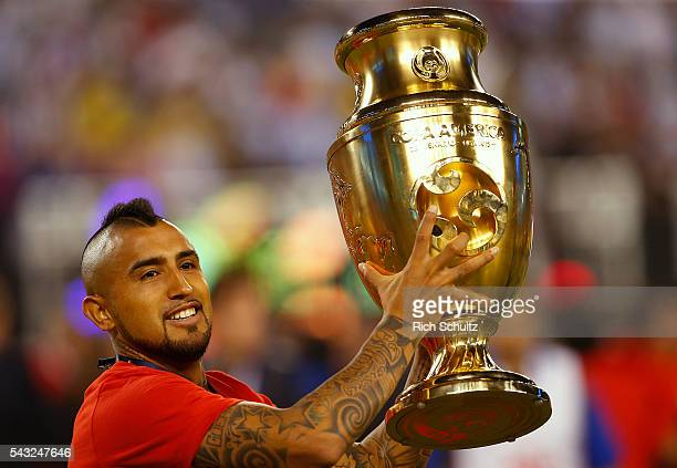 Arturo Vidal of Chile holds the trophy after winning the championship match between Argentina and Chile at MetLife Stadium as part of Copa America...