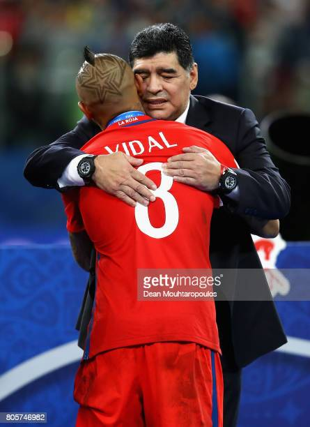 Arturo Vidal of Chile is embraced by Diego Maradona at the award ceremony during the FIFA Confederations Cup Russia 2017 Final between Chile and...