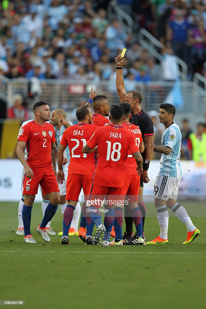 Arturo Vidal of Chile is given a yellow card by referee Daniel Fedorczuk during a group D match between Argentina and Chile at Levi's Stadium as part...