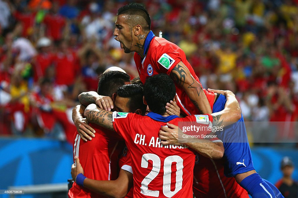Arturo Vidal of Chile jumps on a group of teammates celebrating their first goal by Alexis Sanchez during the 2014 FIFA World Cup Brazil Group B...