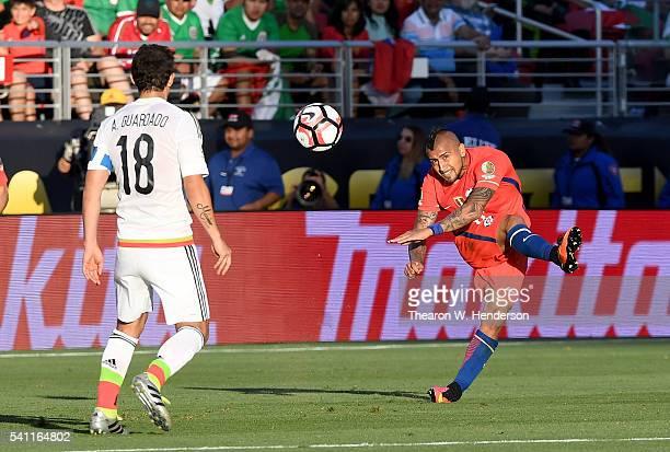 Arturo Vidal of Chile passes the ball up field pass Andres Guaradado of Mexico during the 2016 Copa America Centenario Quarterfinals match play...