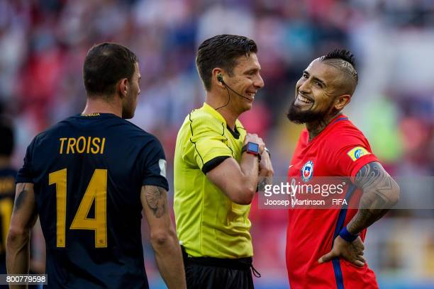 Arturo Vidal of Chile shares a laugh with referee Gianluca Rocchi after receiving a yellow card during the FIFA Confederations Cup Russia 2017 group...