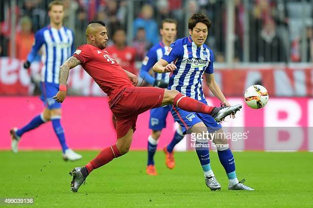 Arturo Vidal of FC Bayern Muenchen and Genki Haraguchi of Hertha BSC battle for the ball during the game between dem FC Bayern Muenchen and Hertha...