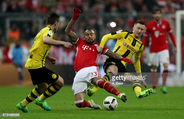Arturo Vidal of FC Bayern Muenchen and Marco Reus of Borussia Dortmund battle for the ball during the DFB Cup semi final match between FC Bayern...