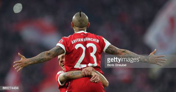 Arturo Vidal of FC Bayern Muenchen celebrates with team mate Rafinha after scoring his team's first goal during the Bundesliga match between FC...