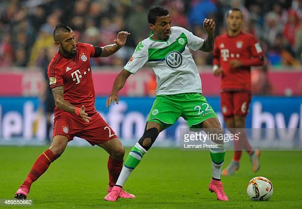 Arturo Vidal of FC Bayern Muenchen challenges Luiz Gustavo of VfL Wolsburg during the Bundesliga match between FC Bayern Muenchen and VfL Wolfsburg...