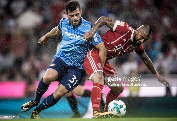 Arturo Vidal of FC Bayern Muenchen is challenged by Kevin Volland of Leverkusen during the Bundesliga match between FC Bayern Muenchen and Bayer 04...