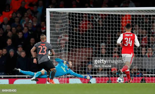 Arturo Vidal of FC Bayern Muenchen scores his team's fifth goal against goalkeeper David Ospina of Arsenal during the UEFA Champions League Round of...