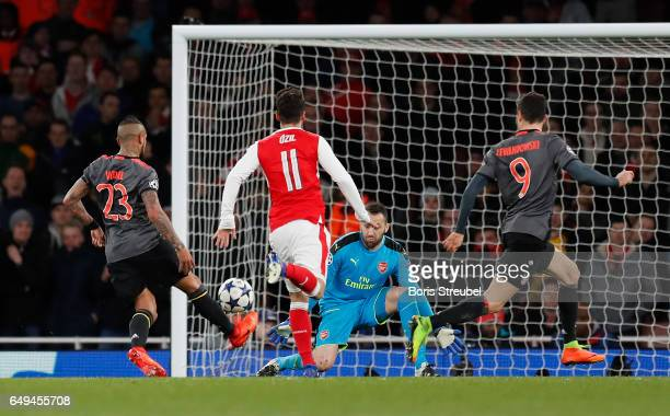 Arturo Vidal of FC Bayern Muenchen scores his team's fourth goal against goalkeeper David Ospina of Arsenal during the UEFA Champions League Round of...