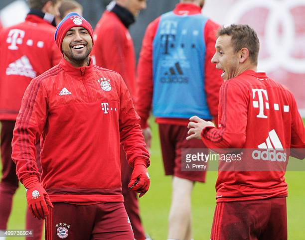 Arturo Vidal of FC Bayern Muenchen shares a laugh with Rafinha during training at FC Bayern Muenchen training grounds on December 3 2015 in Munich...