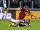 Arturo Vidal of FC Juventus falls in front of Kevin Strootman of AS Roma during the Serie A match between Juventus and AS Roma at Juventus Arena on...