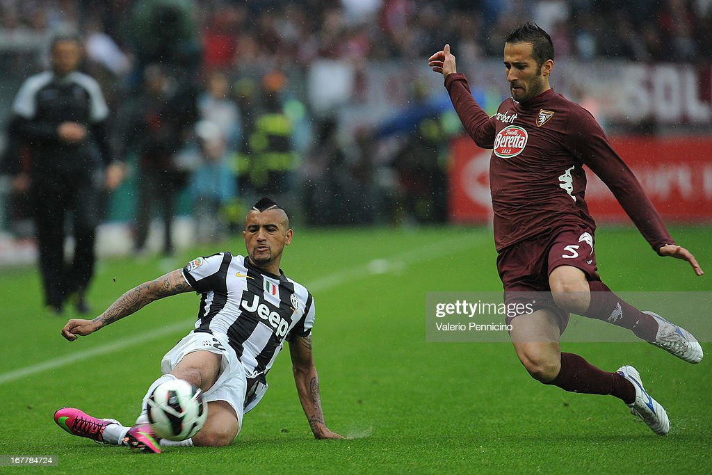 Arturo Vidal (L) of Juventus in action against Valerio Di Cesare of Torino FC during the Serie A match between Torino FC and Juventus at Stadio Olimpico di Torino on April 28, 2013 in Turin, Italy.