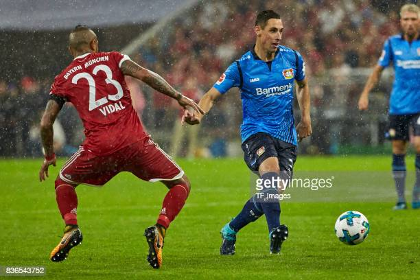 Arturo Vidal of Muenchen and Dominik Kohr battle for the ball during the Bundesliga match between FC Bayern Muenchen and Bayer 04 Leverkusen at...