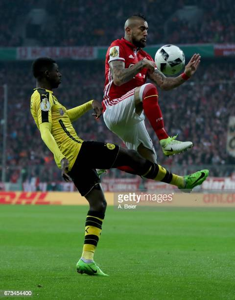Arturo Vidal of Muenchen and Ousmane Dembele of Dortmund battle for the ball during the DFB Cup semi final match between FC Bayern Muenchen and...