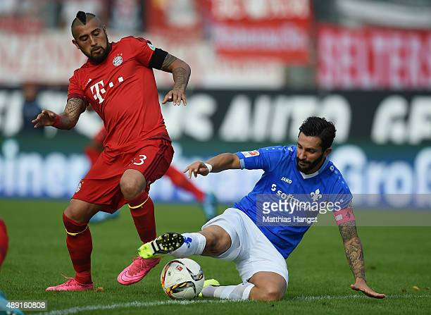 Arturo Vidal of Muenchen is challenged by Aytac Sulu of Darmstadt during the Bundesliga match between SV Darmstadt 98 and FC Bayern Muenchen at...