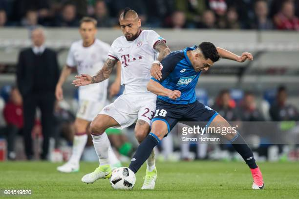 Arturo Vidal of Muenchen is challenged by Nadiem Amiri of Hoffenheim during the Bundesliga match between TSG 1899 Hoffenheim and Bayern Muenchen at...