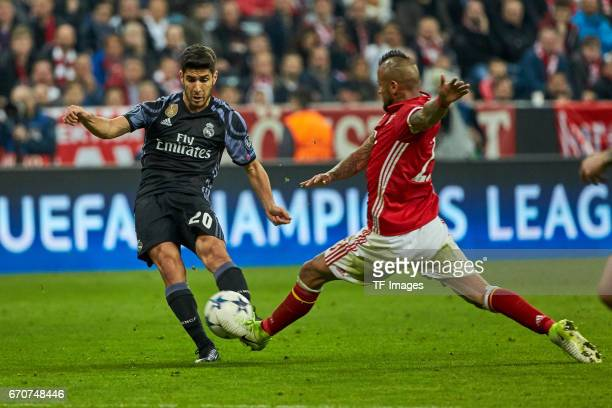 Arturo Vidal of Munich and Marco Asenso of Real Madrid battle for the ball during the UEFA Champions League Quarter Final first leg match between FC...