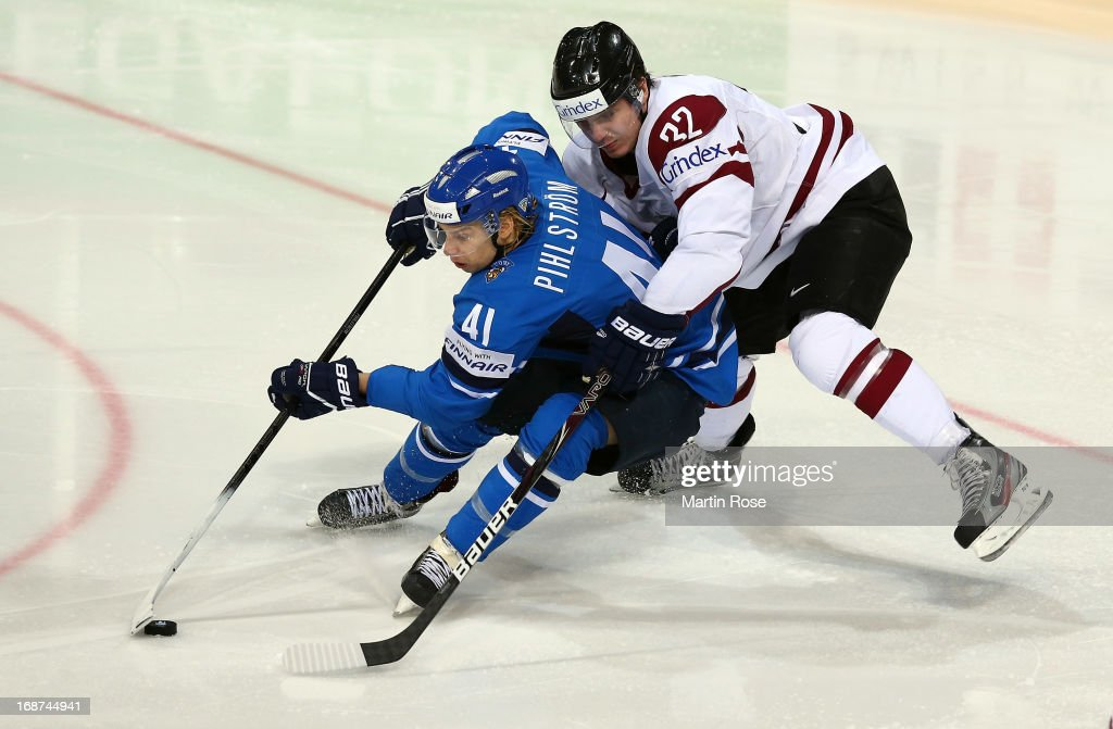 Arturs Kulda (R) of Latvia and Antti Pihlstrom (L) of Finland battle for the puck during the IIHF World Championship group H match between Latvia and Finland at Hartwall Areena on May 14, 2013 in Helsinki, Finland.