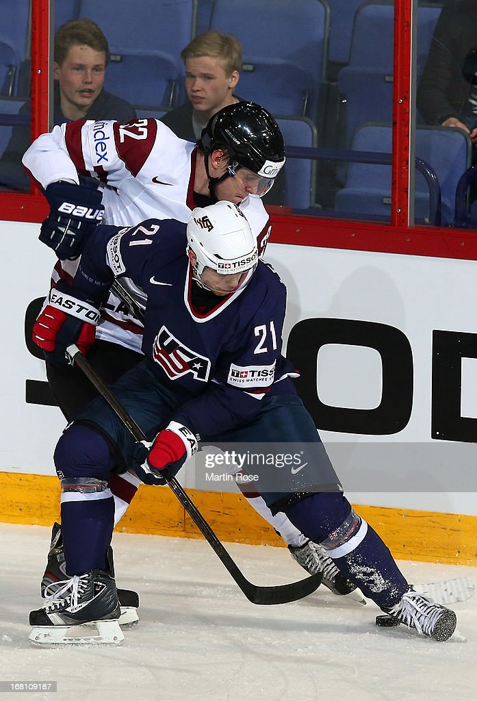 Arturs Kulda (#32) of Latvia and Drew LeBlanc (#21) of USA battle for the puck during the IIHF World Championship group H match between Latvia and USA at Hartwall Areena on May 5, 2013 in Helsinki, Finland.