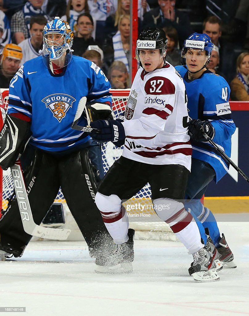 Arturs Kulda (#32) of Latvia and Jarno Koskiranta (#40) of Finland battle for position during the IIHF World Championship group H match between Latvia and Finland at Hartwall Areena on May 14, 2013 in Helsinki, Finland.