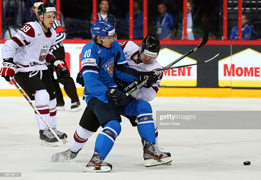 Arturs Kulda (R) of Latvia and Jarno Koskiranta (#40) of Finland battle for the puck during the IIHF World Championship group H match between Latvia and Finland at Hartwall Areena on May 14, 2013 in Helsinki, Finland.