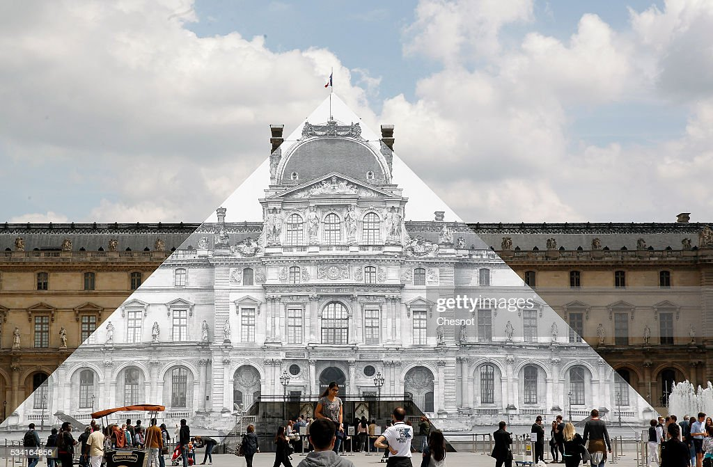 Artwork of French street artist and photographer JR is displayed on the Louvre Pyramid on May 25, 2016 in Paris France. French street artist JR has installed a huge photographic collage on the Louvre pyramid for making it disappear and creating a giant optical illusion through an anamorphosis, a technique that allows to appear or disappear a work.
