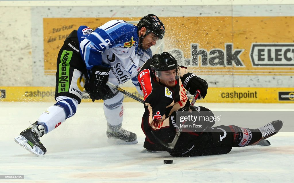 Artyom Ternavsky (R) of Hannover and Calvin Elfring (L) of Straubing battle for the puck during the DEL match between Hannover Scorpions and Straubing Tigers at TUI Arena on January 13, 2013 in Hanover, Germany.
