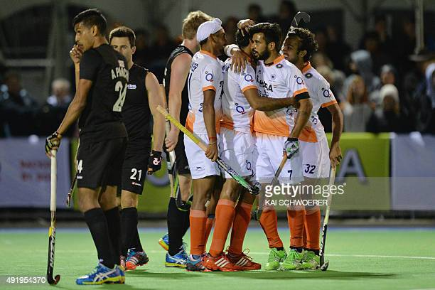 Arun Panchia and Kane Russell of New Zealand look on while Team India celebrate their winning goal during the international men's hockey test match...