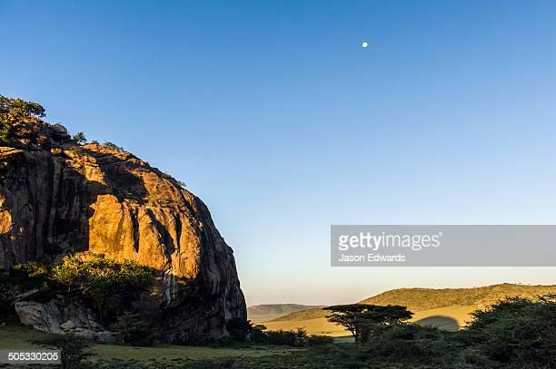 Moonrise at dawn over a rocky outcrop on the savannah plain.