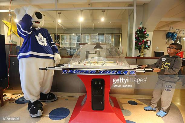 TORONTO ON DECEMBER 5 Arvin Harricharin gets the better of Carlton the Bear on table hockey as the Toronto Maple Leafs visit Sick Kids Hospital...