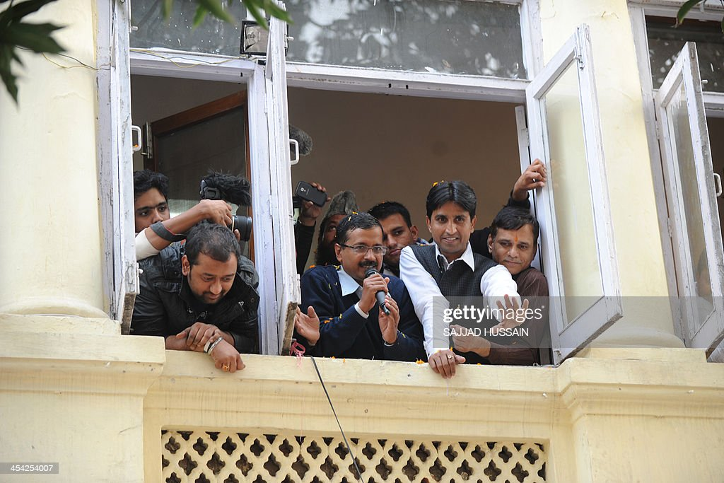 Arvind Kejriwal (C, holding microphone), leader of the Indian Aam Aadmi Party (Common Man's Party), addresses supporters from his office while surrounded by party members after winning the state assembly election against incumbent Sheila Dikshit in New Delhi on December 8, 2013. New Delhi's long-serving Chief Minister Sheila Dikshit lost her seat Sunday to the leader of a new anti-corruption party, state election results showed. Arvind Kejriwal, leader of the Aam Aadmi Party (Common People's Party), took an unassailable lead, winning 37,062 votes against 16,061 for Dikshit, according to the electoral commission.