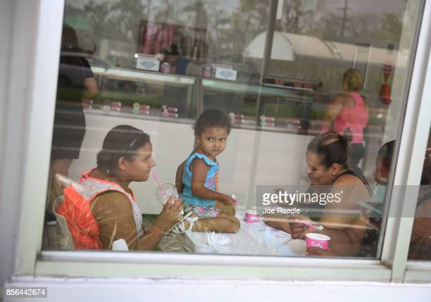 Arwen Martinez Gia Martinez and Kriss Hernandez enjoy an ice cream at a BaskinRobbins that is using a generator for electricity in the aftermath of...