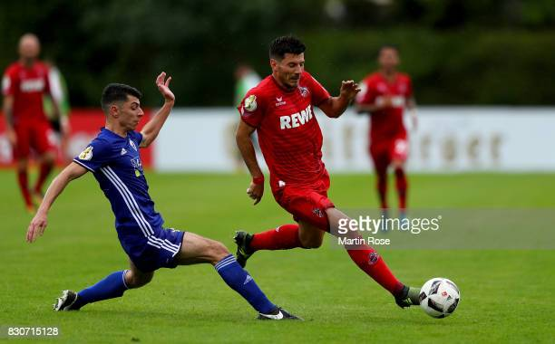 Arwin Hashemi of Leher TS and Milos Jojic of Koeln battle for the ball during the DFB Cup first round match between Leher TS and 1 FC Koeln at...