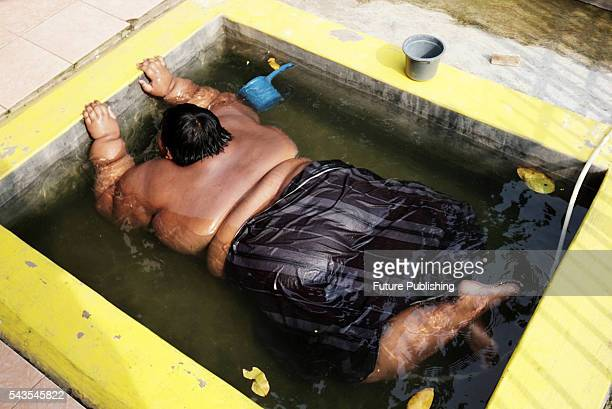 Arya Permana 10yearold who weights 192 kilograms bath in a small pool in front home on June 13 2016 in West Java Indonesia A 10YEAROLD from Indonesia...