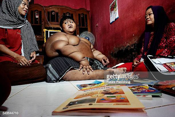 Arya Permana 10yearold who weights 192 kilograms learning with his teacher in his home on June 13 2016 in West Java Indonesia A 10YEAROLD from...