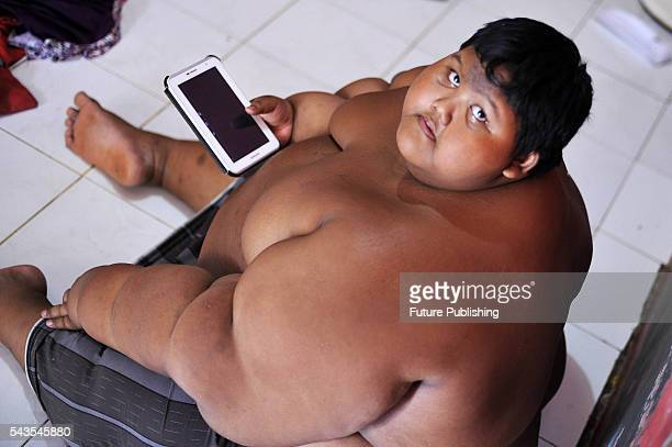 Arya Permana 10yearold who weights 192 kilograms playing game in his tablet in his home on June 13 2016 in West Java Indonesia A 10YEAROLD from...