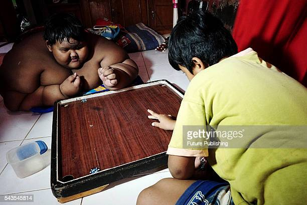 Arya Permana 10yearold who weights 192 kilograms playing game with his friend in his home on June 13 2016 in West Java Indonesia A 10YEAROLD from...