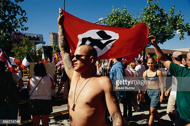 Aryan Nations demonstrators march through the streets of Coeur d'Alene Idaho with a Nazi flag They are joined by Ku Klux Klansmen and other white...