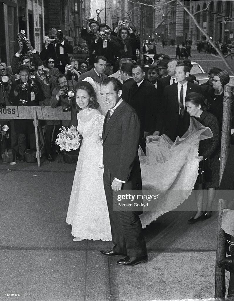 As a crowd of onlookers takes photographs American president-elect <a gi-track='captionPersonalityLinkClicked' href=/galleries/search?phrase=Richard+Nixon&family=editorial&specificpeople=92456 ng-click='$event.stopPropagation()'>Richard Nixon</a> (1913 - 1994) escorts his daughter Julie into the Marble Collegiate Church in Manhattan for her wedding to David Eisenhower, New York, December 22, 1968. The couple were married by Norman Vincent Peale.