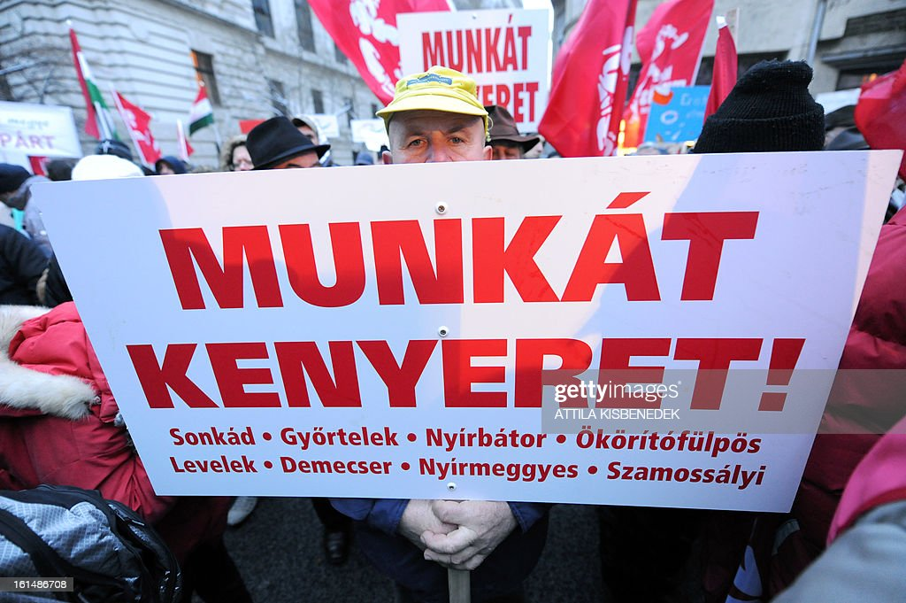 As a local man holds a placard which reads ''Work, bread', participants of the 'Hunger march' near the Hungarian parliament building in Budapest on February 11, 2012 during the first meeting of the Hungarian Parliament this year. Demonstrators, who arrived on foot from several Hangarian cities to protest against the Hungarian government's economy and financial policy.