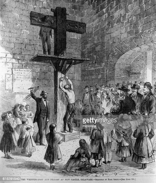 As a morbid crowd watches a law enforcement official whips a criminal tied to the whipping post Up above another man is held in the pillory New...