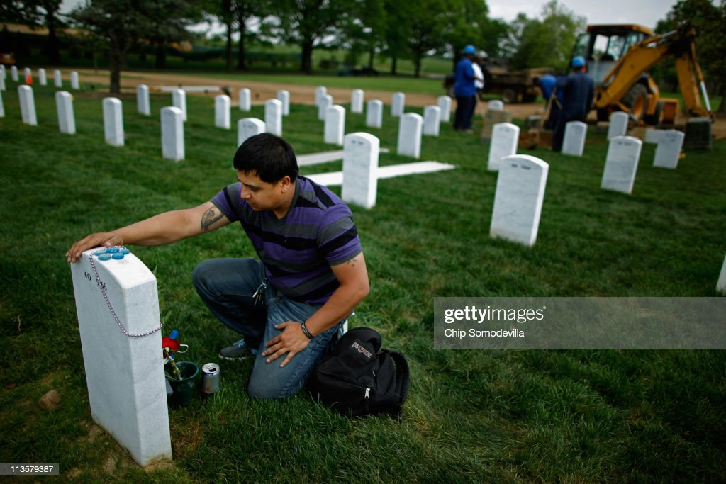 As a new grave is filled in with dirt behind him, Ricky Parada of Stafford, Virginia, visits the grave of his brother, U.S. Marine Corporal Nicholas Parada Rodriguez, at Arlington National Cemetery May 3, 2011 in Arlington, Virginia. After hearing the news about the death of Osama Bin Laden, Ricky Parada thought of his brother said to himself, 'Man, I've got to go and talk to him.' Parada Rodriguez was killed May 16, 2010 during the Marja offensive in Afghanistan. It was his third combat tour and second tour of Afghanistan.