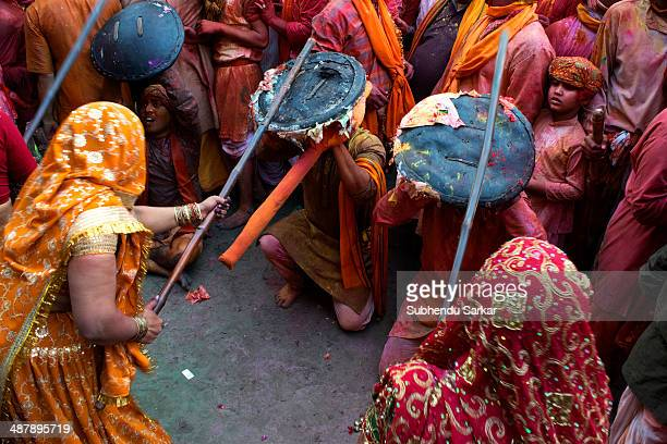 As a part of Holi in Barsana women beat the men of Nandgaon who are carrying shields with sticks on the first day Barsana a village near Mathura in...