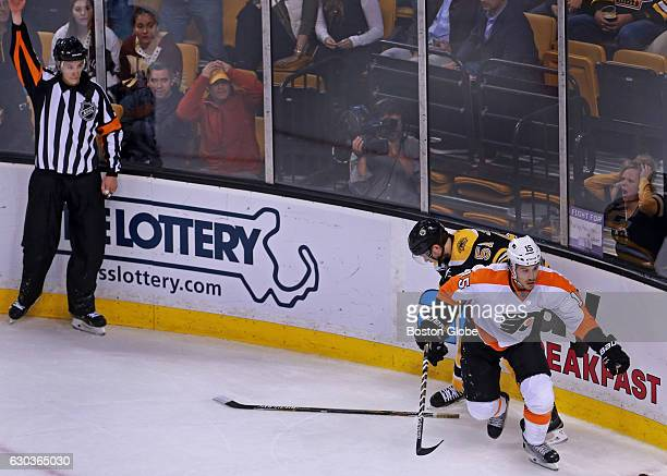 As a referee signals for the penalty fans in the front row react in disbelief as the Bruins' Ryan Spooner is sent off on a penalty late in the...